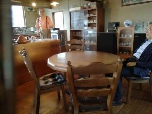 玄豆屋さん2階のカフェ。木の丸テーブルと椅子。奥にキッチン。