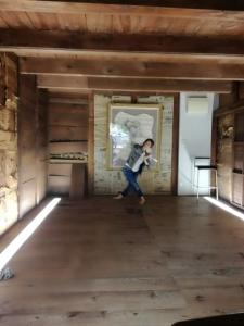 蔵の中で脚をクロスさせ、手を合わせたポーズをする中村明日香。