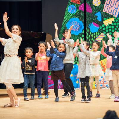 NPO法人あっちこっち主催『こどものためのアート・ダンス・音楽ワークショップ2017』ダンス担当 @戸塚区民文化センター Photo / Taira Tairadate 舞台上、背景はクリスマスのカラフルなアート。子どもたちとスパニッシュ風ダンスをする中村明日香。