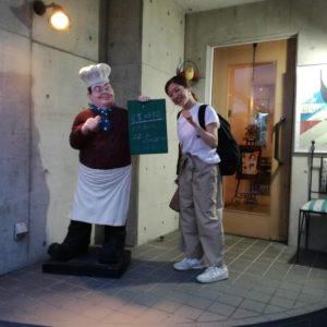 洋食屋さんの前、シェフのキャラクターと同じ様な自分を指すポーズをする中村明日香