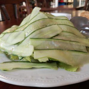 薄くスライスされた沢山のキュウリに覆われた山盛りのグリーンサラダ