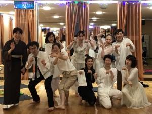 白または黒を基調とした衣装の出演者全員で、各々ポーズ