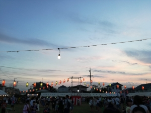 盆踊り会場。夕空にぼうっと浮かぶ提灯と裸電球の灯り。。