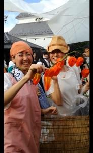 ピンクのエプロン、オレンジの手ぬぐいを頭に巻いたくーさんと、中村明日香。ほおずきが連なる一枝をくーさんと持ち笑顔。