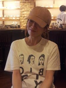 人の顔のイラストが入った白いTシャツに、ベージュのキャップの装いの中村明日香