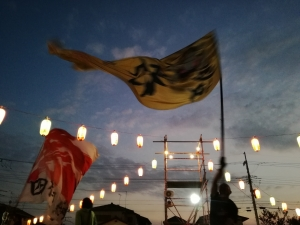 夕空と櫓から伸びる提灯の連なりのコントラスト。翻る2旗の大旗と、操る旗士の身体。