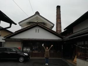 祖父の生家、酒造所の前で両手を上にあげポーズする中村明日香