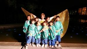 出演した子供たちと。子供たちの後ろで中村はイシスウィング を大きく広げている。