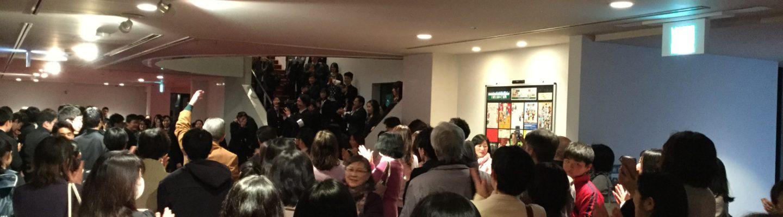 終演後客出しのロビー大盛り上がり。歌い続ける学生。